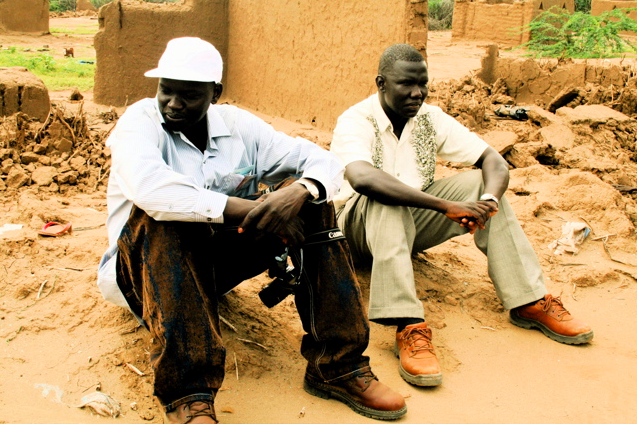 Garang and Gabriel Bol sit on the ruins of their tukul (hut) in Kakuma Refugee Camp. | Credit: COURTESY OF DAVID MORSE