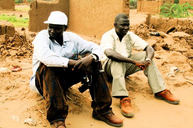 Garang and Gabriel Bol sit on the ruins of their tukul (hut) in Kakuma Refugee Camp. | Credit: COURTESY OF DAVID MORSE
