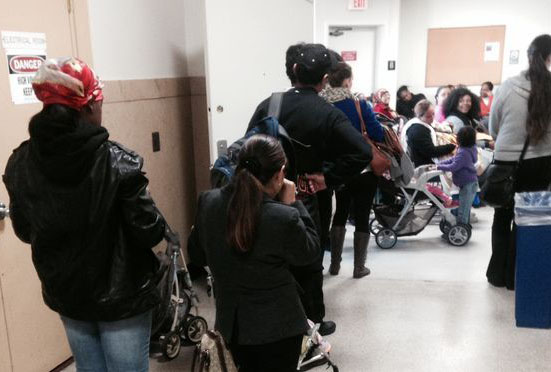 Applicants wait in line to sign up for Medicaid and food stamps outside an overflowing applicaton center at the Essex County Division of Welfare.