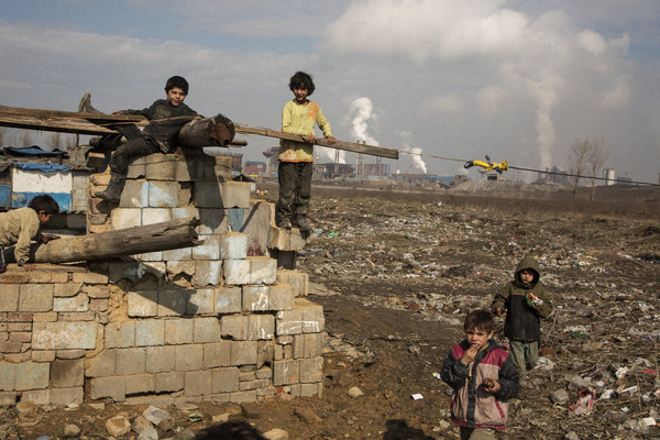 Children playing on a broken wall in the Vel'ká Ida Roma settlement, in eastern Slovakia. The massive US Steel factory is visible in the background. | Credit: COURTESY MARK LUTTON