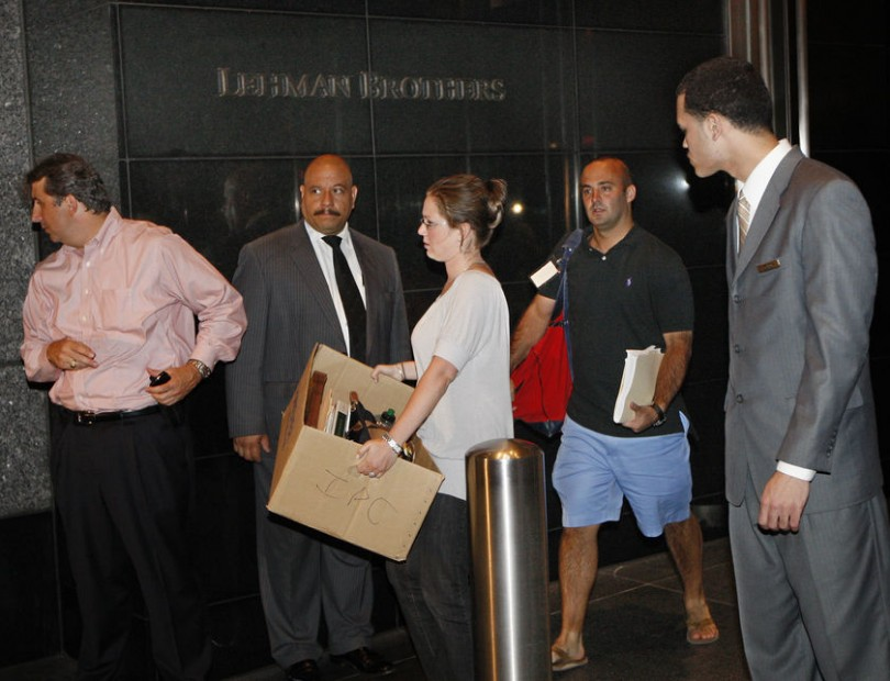 People walk out of the Lehman Brothers building carrying their belongings in New York. | Credit: CHIP EAST/REUTERS