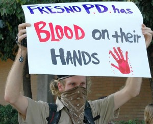 A protester holds up a sign in downtown Fresno during a demonstration in 2009 demanding police accountability after officers shot and killed Fresno resident Lonnie Graham, who was unarmed.