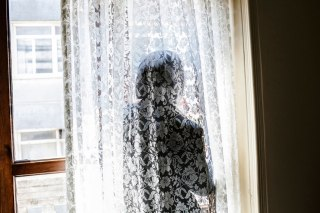"""""""Sabeen,"""" a 37-year-old Syrian, looks out the window of a hotel in Antakya, Turkey. She was detained last year by Syrian government forces and sexually assaulted. 