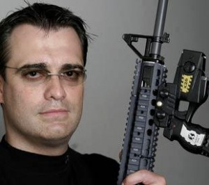 Taser International co-founder and CEO Rick Smith shows how the company's X-26 Taser can be mounted to a rifle. The X-26 is being used in this manner by the military in Iraq.
