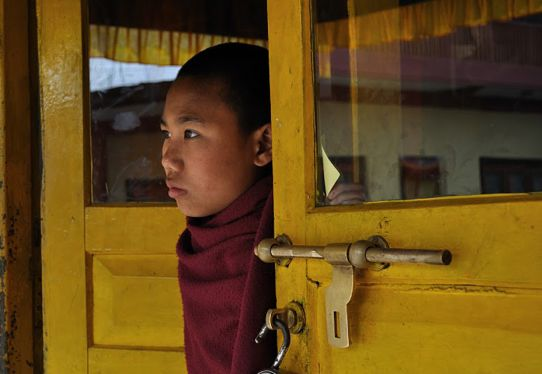 A young monk peers into the courtyard of the Tashiling Tibetan Refugee camp, near Pokhara, Nepal.   Credit: GREG BRUNO