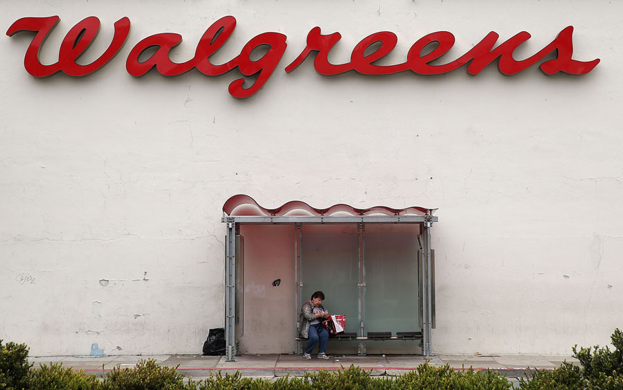 A woman sits in a bus shelter outside of a Walgreens store on July 9, 2015, in San Francisco. | Credit: JUSTIN SULLIVAN/GETTY IMAGES
