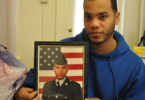 Feliz in his Lancaster apartment holding a photo of himself when he served in the Army. | Credit: GUERNICA