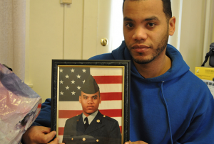 Feliz in his Lancaster apartment holding a photo of himself when he served in the Army.   Credit: GUERNICA
