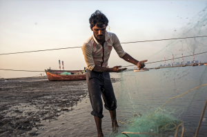 A fisherman at Kutadi Bandar prepares the net for an overnight fishing trip. Locals say the World Bank Group-backed power plant in the distance has depleted fish stocks.
