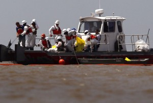 Oil spill cleanup workers adjust an oil boom at South Pass near the mouth of the Mississippi River on May 14, 2010 near Venice, Louisiana. | Credit: JOHN MOORE/GETTY IMAGES