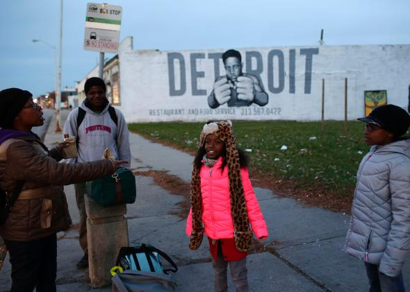 Tonja Boyd (left) talks with her daughters Nemyla Boyd (center) and Alexandria Boyd (right) as they wait at a bus stop on Nov. 7, 2014 in Detroit. | Credit: JOSHUA LOTT/GETTY IMAGES