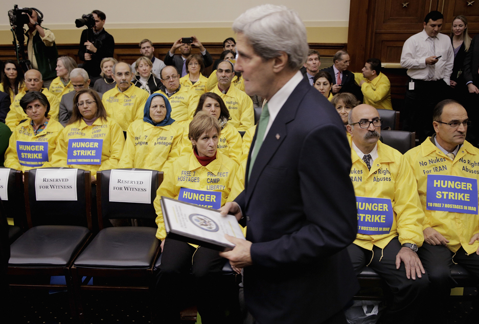 Secretary of State John Kerry walks past members of MEK at a House Foreign Affairs Committee on December 10, 2013. | Credit: TJ KIRKPATRICK/STRINGER/GETTY IMAGES