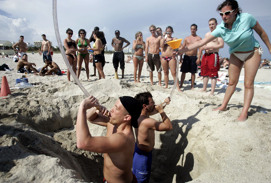 MIAMI BEACH - MARCH 16: Mathew Lakatos (L) and Brett Witmer from Shippensburg University use a funnel to drink beer during spring break on South Beach March 16, 2007 in Miami Beach, Florida. Students from universities and colleges around the country are attending spring break which starts at the end of February and into mid-April.