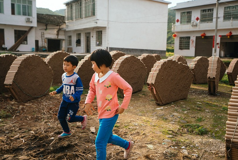 Children run between stacks of fireworks shells in Bixi village, China, on May 11. Many former child laborers who survived fireworks accidents are still seeking compensation.