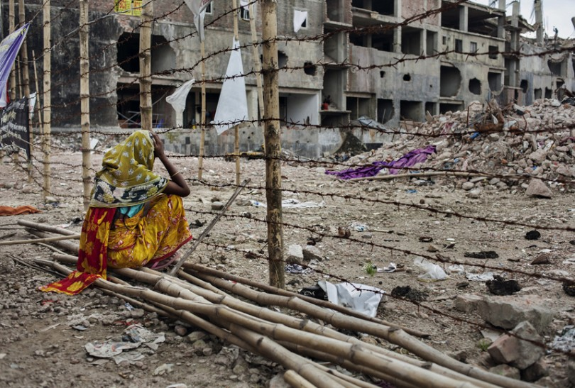 The mother of a missing worker — Rina, age 18 — waits for her daughter in front of the barricade at Rana Plaza in Dhaka, Bangladesh, July 24, 2013.