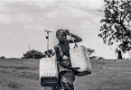 A child carrying water-filled jerricans at the Laufori refugee collection point, on the border of Uganda and South Sudan.