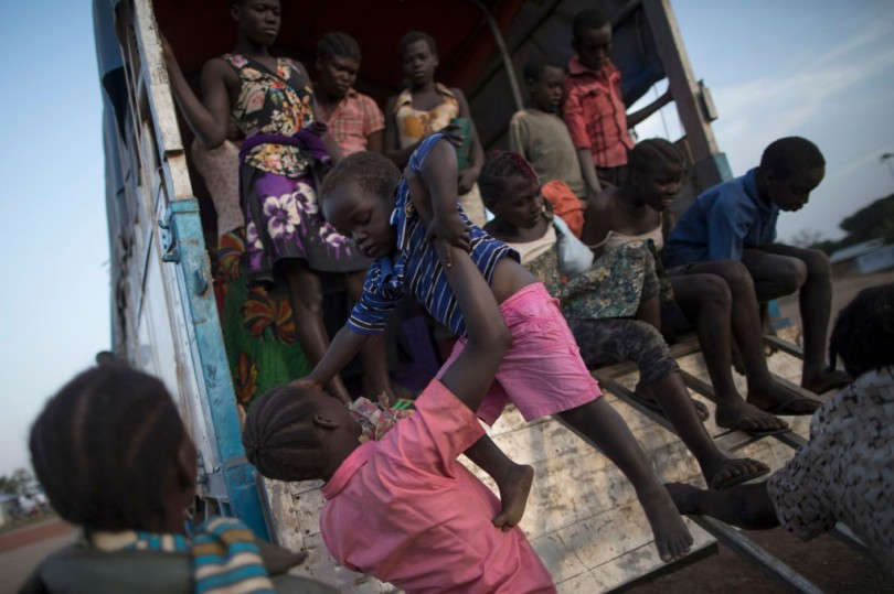 South Sudanese refugee families disembark a bus at the Kuluba Collection Point in Uganda after being brought from the border on February 24, 2017.