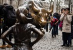 People take photographs of the 'The Fearless Girl' statue as it stands across from the iconic Wall Street charging bull statue.