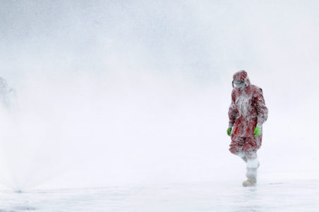 A recruit walks through aqueous film forming foam (AFFF) after a test of the AFFF sprinkler systems aboard the flight deck of the aircraft carrier USS Ronald Reagan while off the coast of California May 19, 2010.